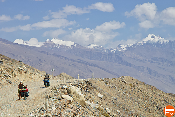 two riders cycling toward high mountains