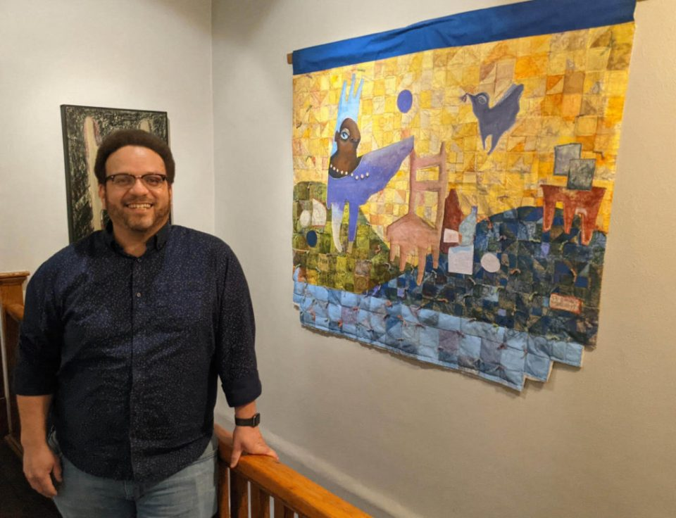 Robby with his art at Lafayette Flats Boutique Vacation Rentals.