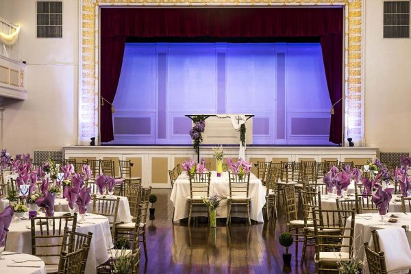 The stage and Bride & Grooms table in the Grande Ballroom. The Grande Ballroom can seat up to 500 people, with room for dance and dinner. With two bars, upstairs and down, a bridal suite, on-floor restrooms, and even a mezzanine overlooking the main floor.