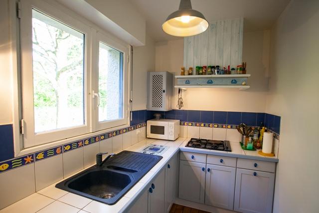 Une jolie cuisine à la couleur bleu avec tout l'équipement nécessaire pour profiter de ses vacances