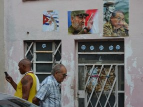 HAB110. LA HABANA (CUBA), 02/12/2016.- Dos hombres caminan frente a una casa con afiches de Fidel castro (c), el Presidente de Cuba, Raul Castro (d), y el Papa Francisco (i) hoy, viernes 2 de diciembre de 2016, en La Habana (Cuba). La urna con las cenizas de Castro, que partió desde La Habana, se encuentra en viaje de cuatro días por la isla hasta la Ciudad de Santiago en donde se celebrara su funeral el domingo 4 de diciembre. EFE/Rolando Pujol