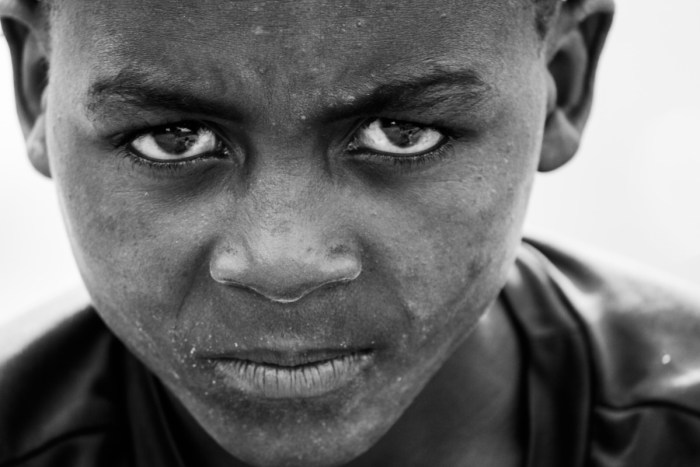 man person black and white photography boy kid alone male portrait child dirty black monochrome facial expression smile close up face eye head look angry mad emotion monochrome photography portrait photography