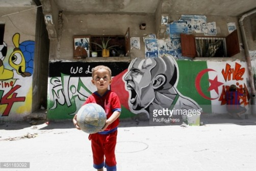 451183092-palestinian-boy-plays-with-a-ball-in-front-gettyimages