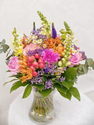 Flot blomster buket i blandede farver. Bundet af sæsonens blomster