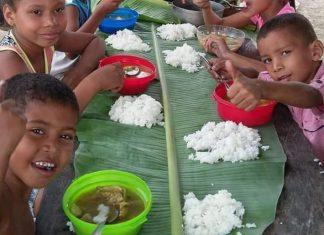Niños guajiros que reciben los alimentos en hojas de bijao.
