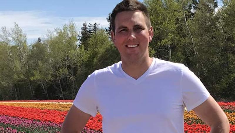 Bastiaan Arendse, bulb specialist, standing in a field of pink, red, yellow and orange tulips.