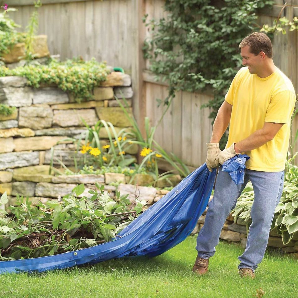 Man hauling garden debris on tarp