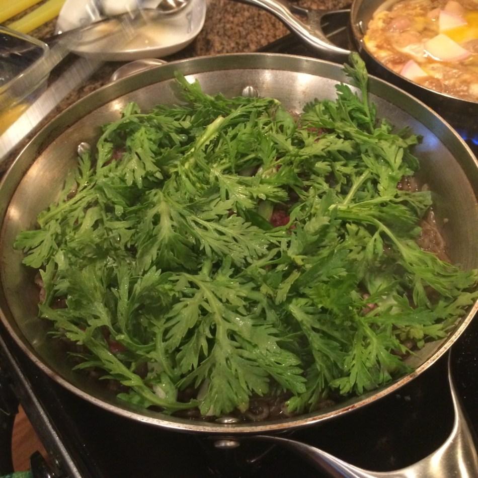 garland chrysanthemum leaves cooking in a metal wok