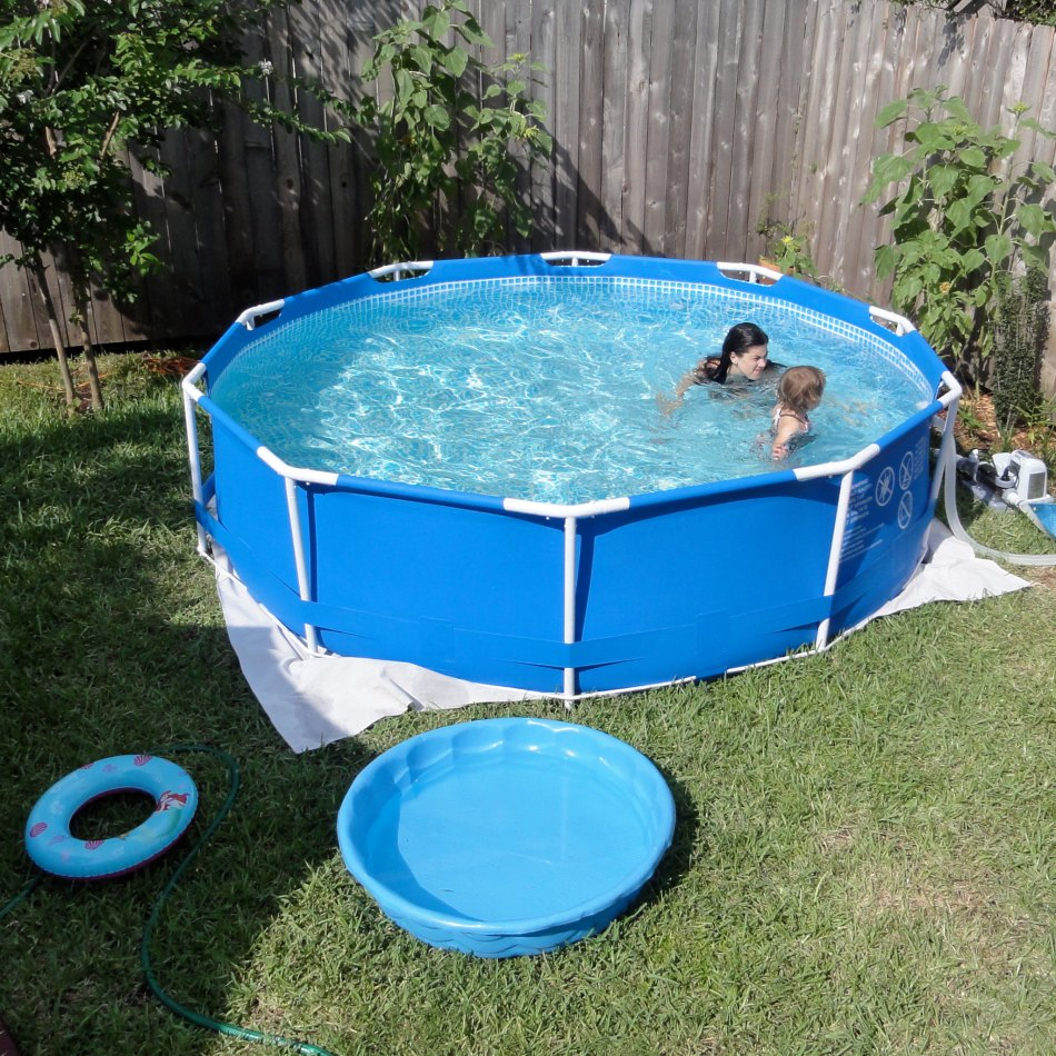 Above ground pool and kiddie pool on a lawn.