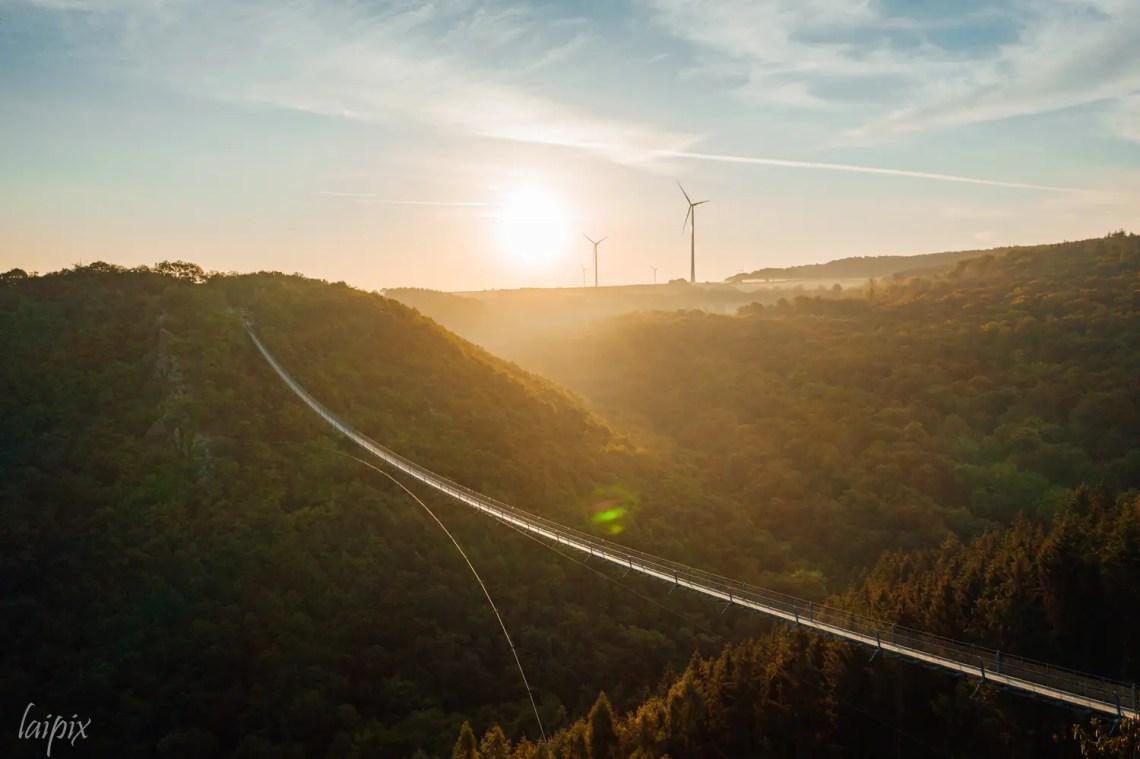 Sonnenaufgang Hängeseilbrücke über grüne Landschaft Hunsrück