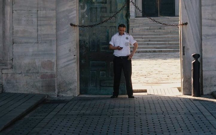 security guard standing at arched gates of historic building