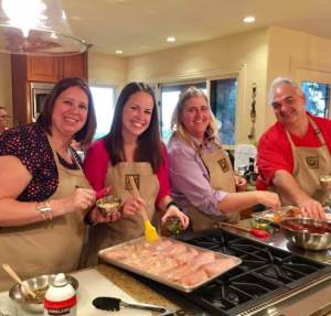 Team building clients preparing chicken for an event dinner