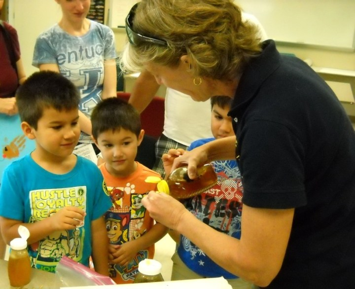 Beth Wilson pours out honey samples for young visitors at the event