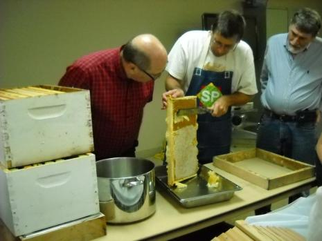 Robert Martin observes while Ray Tucker uses a knife to uncap the cells in a honey frame