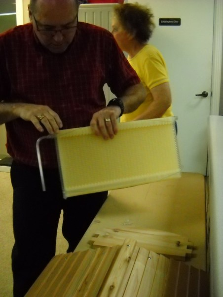 Dr. Martin demonstrates inserting the metal bar which cracks open the plastic comb, allowing honey to flow