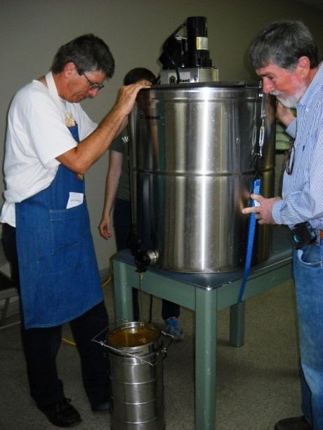 Ray tucker and Doug Brock steady the honey extractor as frames in the barrel are spun and honey flows out into a sieve placed over a metal container