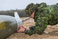A participant in Exercise Taz Tornado, an advanced conventional munitions disposal exercise, prepares to open the hatch of a bomb during a scenario at Jimmy Lake Range, Cold Lake Air Weapons Range, on September 30, 2014. Photo: Corporal Manuela Berger