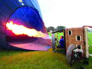 Balloon pilot Tom Warren shoots flames into the interior of a balloon, to heat the air in the balloon. The hot air is what gives the balloon its lift. (B.C. Manion/Staff Photo)