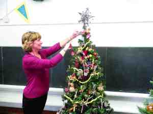 Suzin Carr adjusts a tree decorated by the Steinbrenner High School Student Ambassadors. It's just one of many on display at the Old Lutz School during Christmas season. (Michael Murillo/Staff Photo)