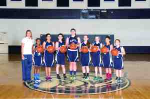 The Academy at the Lakes Middle Division girls' basketball team claimed its second consecutive league championship by achieving a perfect season. From left are coach Marla Oliver and players Zoe Moore, Zainab Nawaz, Lexi Fernandez, Lexi Kilfoyl, Amelia Cozzolino, Kendra Falby, Jordan Angeles and Bella Robichaux. Not pictured: Haneen McNamee. (Courtesy of Academy at the Lakes)