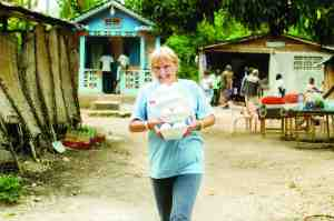 Cindy Oelke carries containers of food in Haiti. Someday, she'd enjoy seeing Europe. For now, she feels called to do God's work in Haiti.