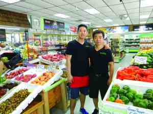 Jeff Kim, right, and his son, Yong Son, sell organic and fresh fruits and vegetables at Natural Market II. (Kathy Steele/Staff Photos)