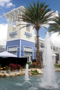 Fountains shoot water into the air as the Market Hall food court towers over the Lagoon Court at the Tampa Premium Outlets.