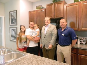 Kyle, Amelia and Melody Marks, left, will wait about six months for their new Lennar home to be built in Connerton. Stew Gibbons, president of Gibbons Group, and Jeff Morin, vice president of sales for Lennar joined them at the newly opened Lennar model home.
