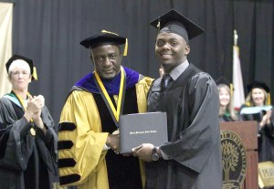 Jamal Roberts (right) is presented with his diploma from Pasco-Hernando State College from Dr. Timothy Beard, the college's president.