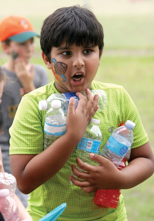 Srinav Nekkanti, 8, carries empty water bottles to the recycle bin after teams finished the tug o' war during Field Day activities. More than 700 students participated.