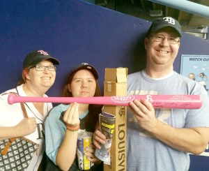 From left, Pam Ingram, her daughter, Abby, and her husband, Keith, show off the new pink Louisville slugger that has Pam's name engraved on it. It was part of the swag she received by winning the Honorary Bat Girl Contest, representing the Tampa Bay Rays. The national contest is sponsored by Major League Baseball.