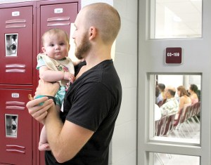 Derek Muscato and his 5-month-old daughter, Ellie Jo, took a break from a seminar on 'Fruit and Vegetable Crops for West Central Florida.' He and his wife, Annie Muscato, are thinking of growing crops on their 30-acre farm.