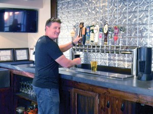 In the Loop Brewing co-owner Joe Traina pours a beer at the Land O' Lakes brewery. (Kathy Steele/Staff Photos)