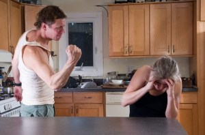 man aggressively facing a woman with his hand in a fist. The woman is cowering, hiding her face.