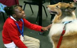 a girl petting a dog, looking happy.