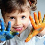 a girl with her hands covered in paint, smiling at the camera.