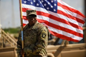A solider carrying the American Flag