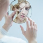 A woman looking into a broken mirror.
