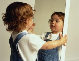 a baby looking into a mirror