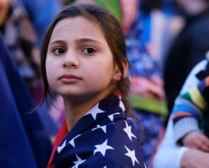 a young girl, wrapped in an American flag.