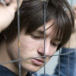 a photo of a young man with his head against a fence, looking defeated