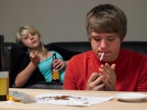 a teenage boy smoking with a teenage girl drinking
