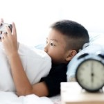 child in bed looking at smartphone