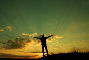 person standing in sunrise with arms outstretched