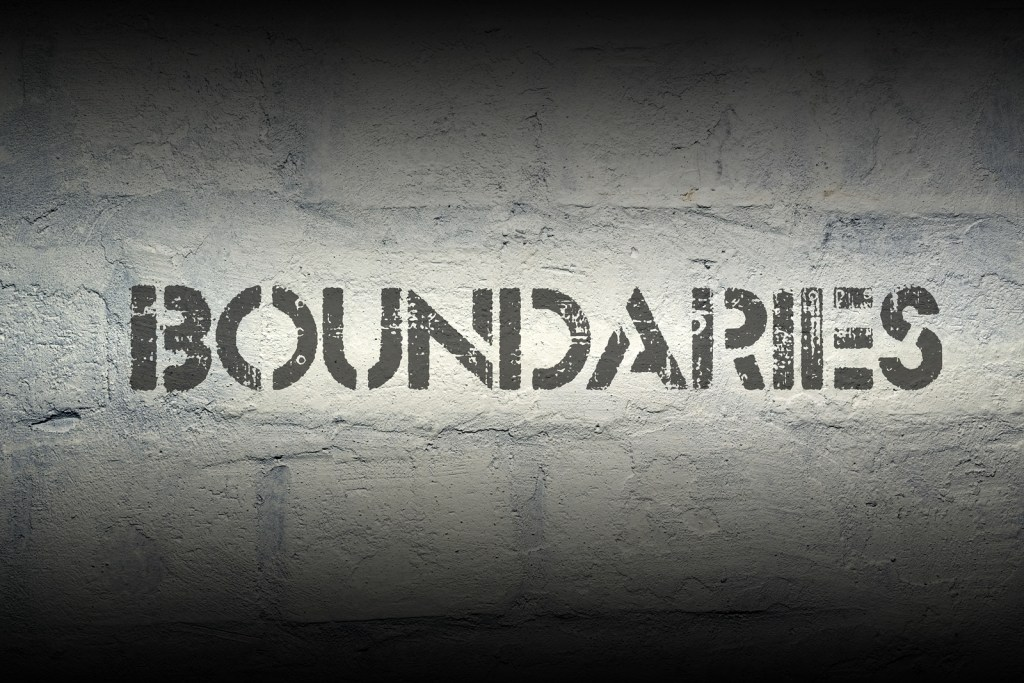 """Boundaries"" stencil print on the grunge white brick wall"