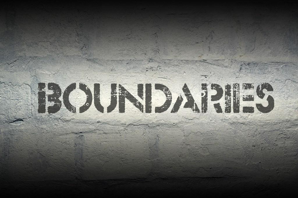 """Boundaries"" stencil print on the grunge white brick wall"