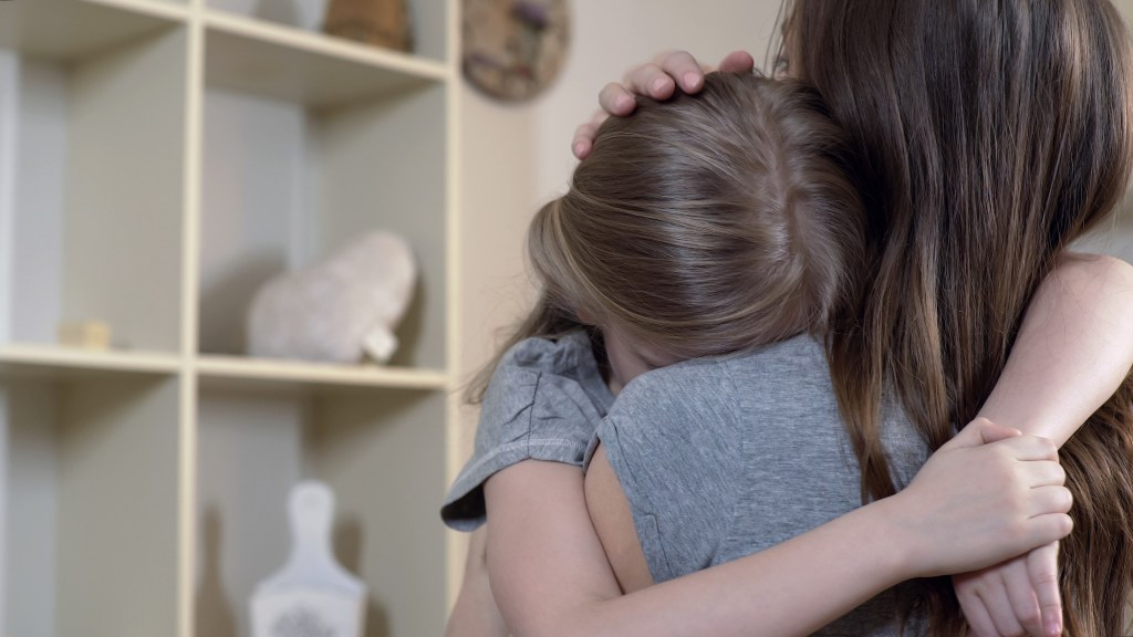 Woman comforting her child carefully, mother hugging sad daughter