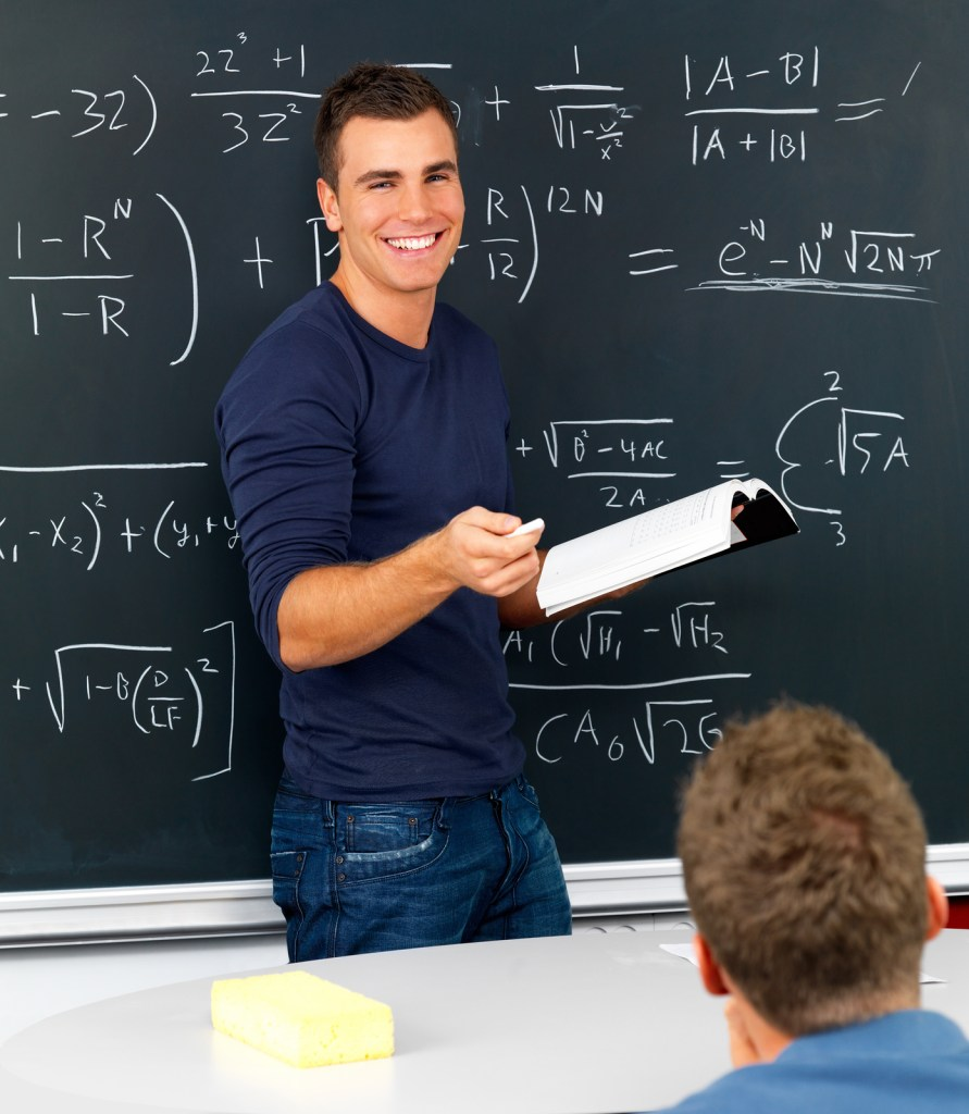 Teacher at chalkboard talking with students