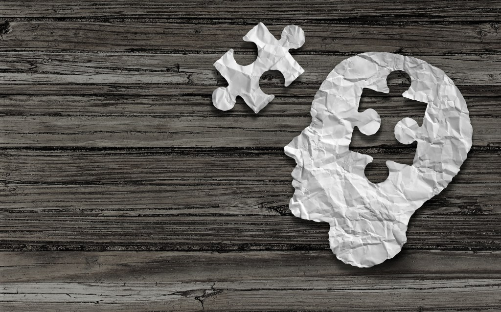 Puzzle and head brain concept as a human face profile made from crumpled white paper with a jigsaw piece cut out
