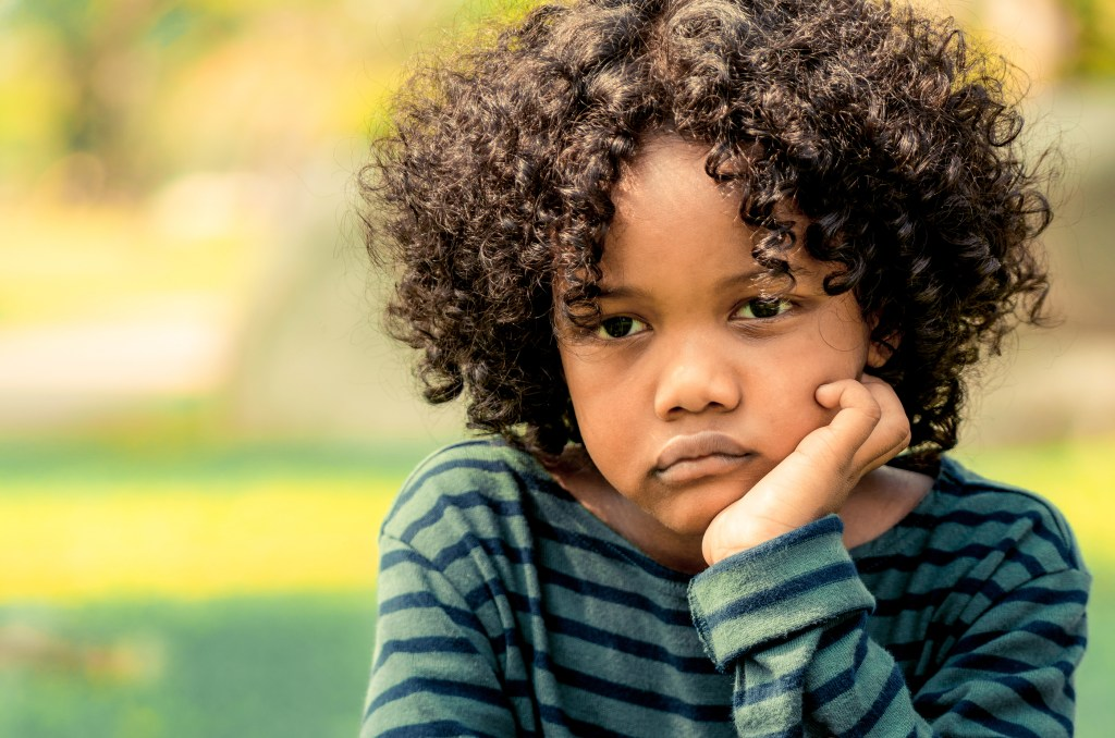 Unhappy little african american kid  showing negative emotion. Child trouble concept.